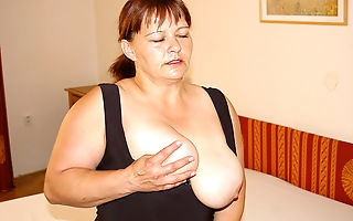 Big breasted mama playing on her bed